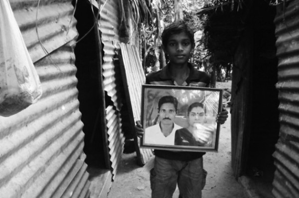 காணாமற்போன தந்தையுடன் தாய் உத்தரை எடுத்துக் கொண்ட படத்துடன் அவர்களின் 14 வயது மகன் யதுசன்.