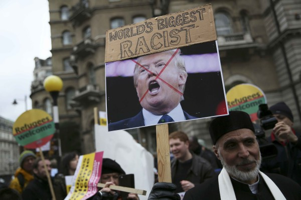 A demonstrator holds a placard of  U.S. presidential candidate Donald Trump during a refugees welcome march in London